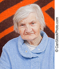 Old lonely woman staying alone at home