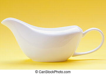 White ceramic gravy boat on a yellow background