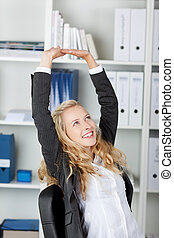 Businesswoman With Arms Raised Sitting In Office -...