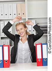 Successful Businesswoman With Arms Raised In Office - Happy...