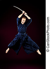 jumping kendoka - Handsome young man practicing kendo. Over...