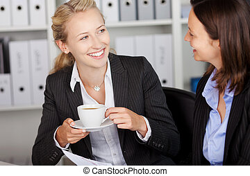 Businesswoman Having Coffee While Looking At Coworker -...