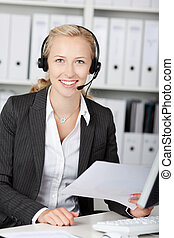 Portrait of young customer service representative using headphones while holding paper at desk