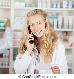 Portrait of young female pharmacist holding prescription...