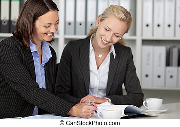 Businesswomen Working On File At Desk - Happy businesswomen...
