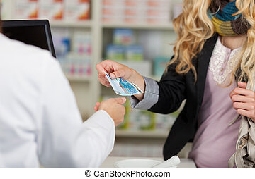 Pharmacist Receiving Money From Woman For Medicines