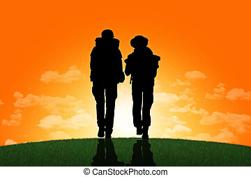 couple of backpackers walking on a top of a hill at sunset -...