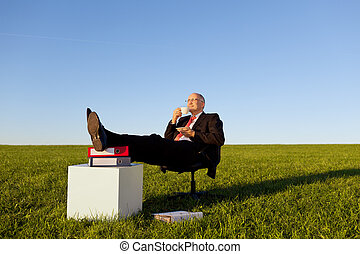 Full length of relaxed businessman enjoying coffee on chair...