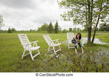 Girl Sitting on Chair in Rain Soaked Yard - An attractive...