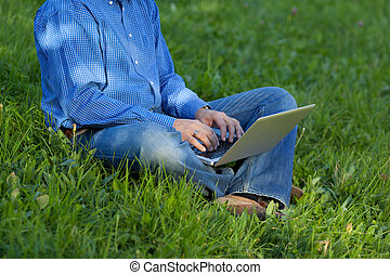 Low Section Of Businessman Using Laptop While Sitting On...