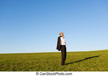 Mature Businessman Standing On Grassy Field - Businessman...