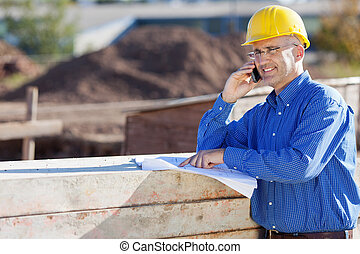 Mature male architect pointing at blueprint while using...