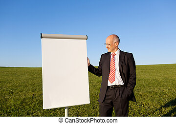 Businessman With Flipchart On Grassy Field - Portrait of...