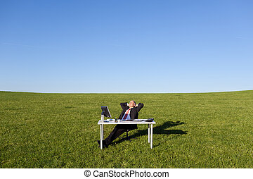 Businessman With Hands Behind Head On Field - Relaxed mature...