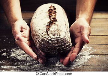 Baker's hands with a bread. Photo with high contrast