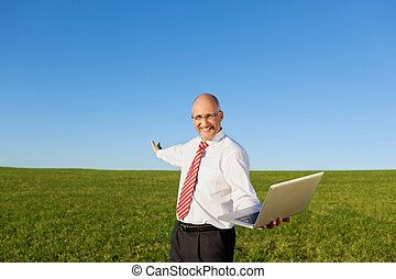 Portrait of excited mature businessman with arms outstretched holding laptop on filed against clear sky