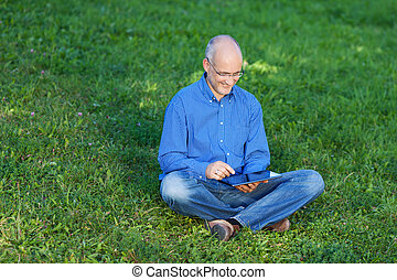 Businessman Using Digital Tablet While Sitting On Grass -...
