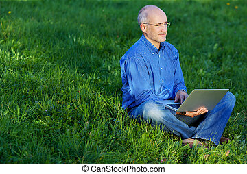 Man Using Laptop While Sitting On Grass - Mature man using...