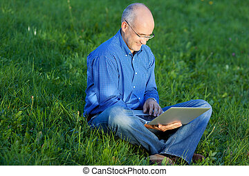 Smiling Businessman Using Laptop While Sitting On Grass -...