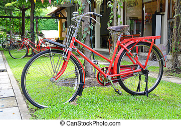 red bicycle on green grass in garden