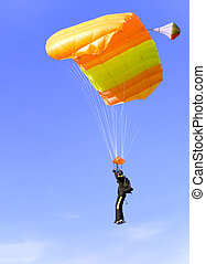 orange parachute - an orange parachute in a blue sky on a...