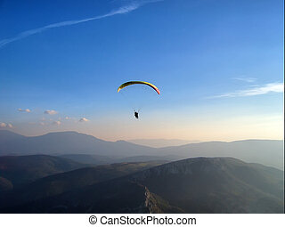 paraglider flying in the thilight