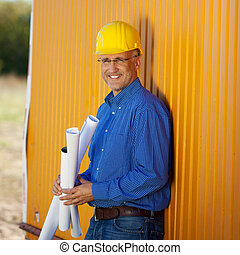 Confident Architect Holding Blueprints While Leaning On...