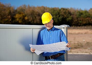 Architect Wearing Hardhat While Examining - Mature male...