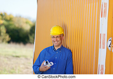 Architect Holding Blueprints While Leaning On Trailer -...