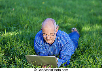 Businessman With Laptop Lying On Grass - Mature businessman...