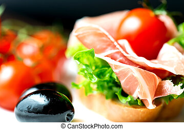 Sandwiches with prosciutto on plate with olive