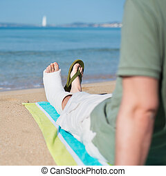 Man with Plaster relaxing on Beach - Injured Man with...