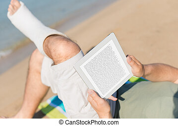 Injured Man relaxing on the beach and reading a book