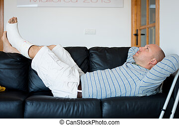 Injured Man Lying on Sofa with leg plaster