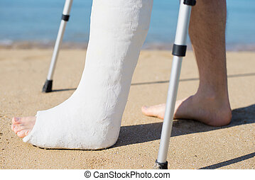 Man with plaster walking on the beach with the help of...