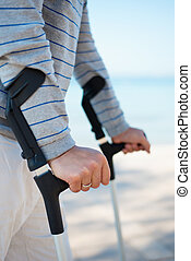 Injured Man standing with Crutches on the beach