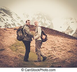 Happy young hiker couple with backpacks in mountains