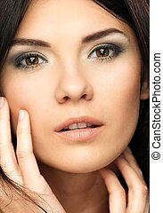 Young beautiful brunette woman with make-up touching her...