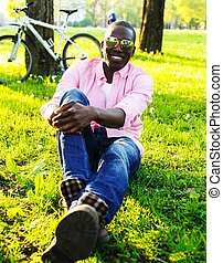 Young happy smiling african american wearing sunglasses with bicycle behind him in a park