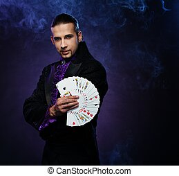Young brunette magician in stage costume showing card tricks...