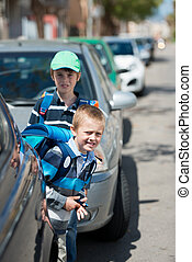 Schoolchildren waiting between the parked car outdoors