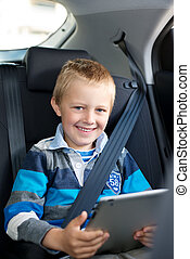 Young boy sitting holding a tablet - Young boy sitting...