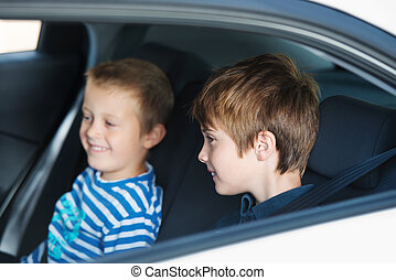 Two children smiling and sitting in the car
