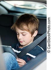 Young boy using a tablet computer while sitting in the back...