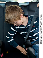 Young little boy buckled up with seatbelt inside the car