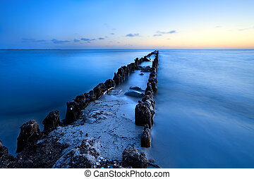 long old wooden dike in North sea at dusk, Netherlands
