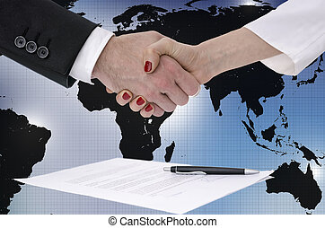 Shaking hands over map of the world - Male and female hands...