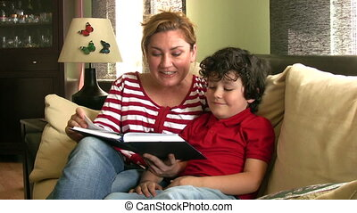 Story time - Mother reading to child sitting on sofa