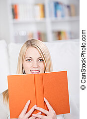 Young Woman Holding Book In Living Room - Portrait of...