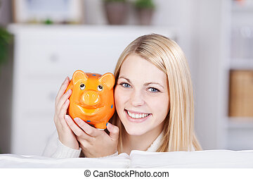 Young Woman Holding Yellow Piggybank - Portrait of happy...